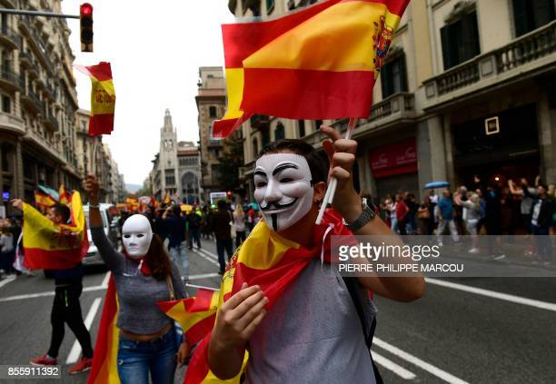 A man wearing a 'Guy Fawkes' mask holds a Spanish flag during a demonstration against independence in Catalonia on September 30 2017 in Barcelona...