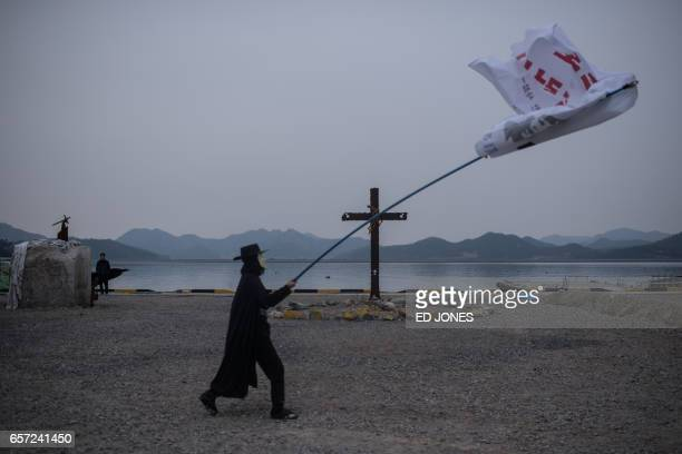 TOPSHOT A man wearing a Guy Fawkes mask waves a flag as he walks past a memorial at a camp for relatives of Sewol ferry victims at Paengmok harbour...