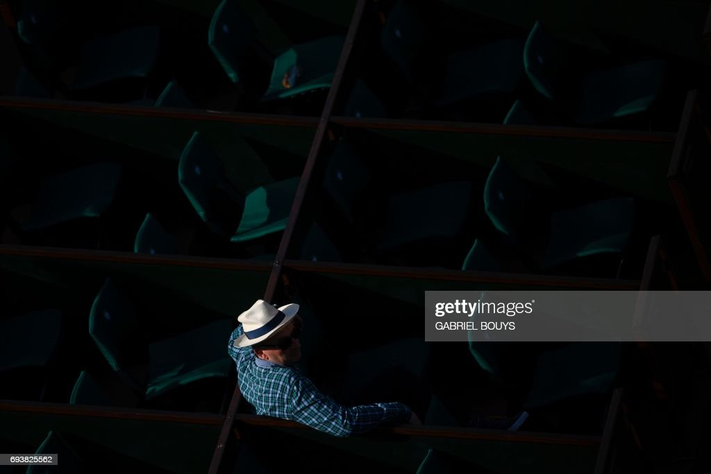 A man wearing a hat attends the semifinal tennis match between Romania's Simona Halep and Czech Republic's Karolina Pliskova at the Roland Garros 2017 French Open on June 8, 2017 in Paris. /