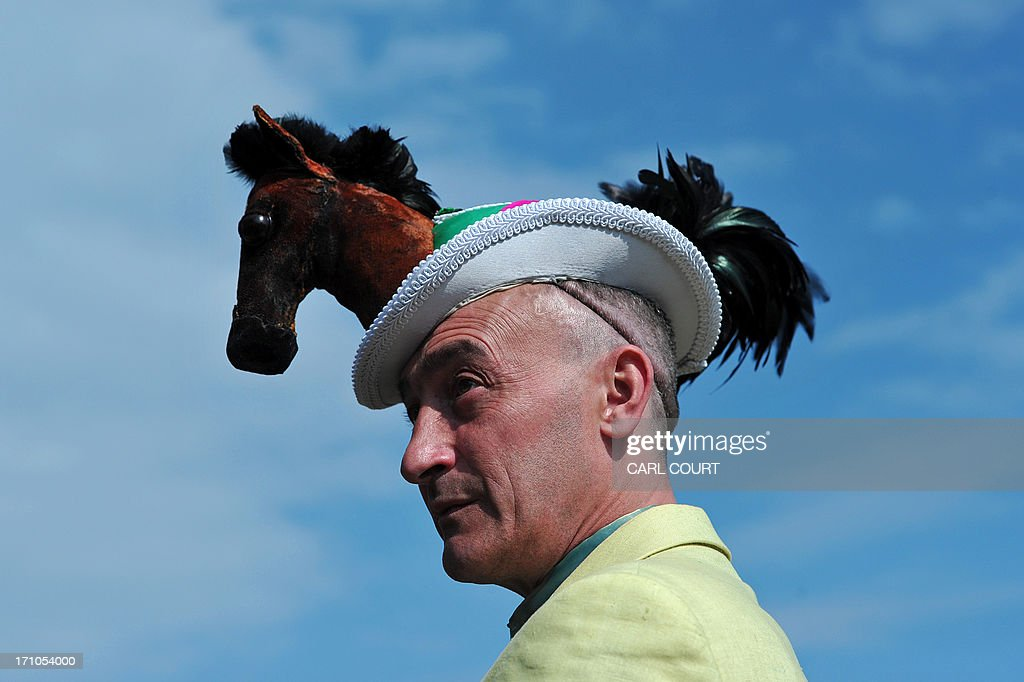 A man wearing a hat decorated with a miniature soft toy horse poses for photographs on the fourth day of the horse racing festival at Royal Ascot in Berkshire, west of London, on June 21, 2013. Horse racing has been held at the famous Berkshire course since 1711 and tradition is a hallmark of the meeting. Top hats and tails remain compulsory in parts of the course while a daily procession of horse-drawn carriages brings the Queen to the course.