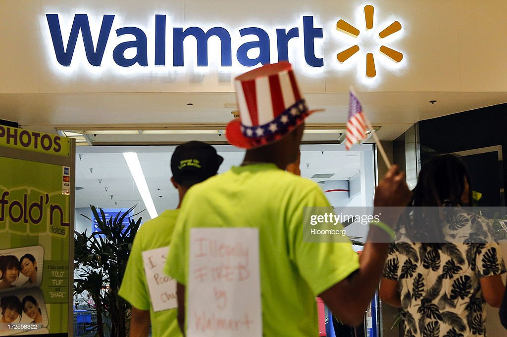 A man wearing a hat decorated with stars and stripes joins protesters during a demonstration outside a Wal-Mart Stores Inc. location in Los Angeles, California, U.S., on Tuesday, July 2, 2013. Southern California community supporters joined Wal-Mart Stores Inc. workers to protest against alleged illegal violations of employees labor rights and freedom of speech. Photographer: Patrick T. Fallon/Bloomberg via Getty Images