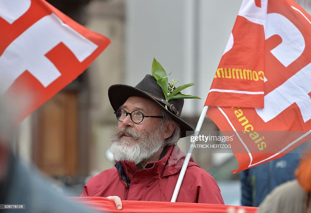 A man wearing a hat with a bouquet of lily of the valley demonstrates during the traditional May Day rally in Strasbourg, eastern France, on May 1, 2016. / AFP / PATRICK