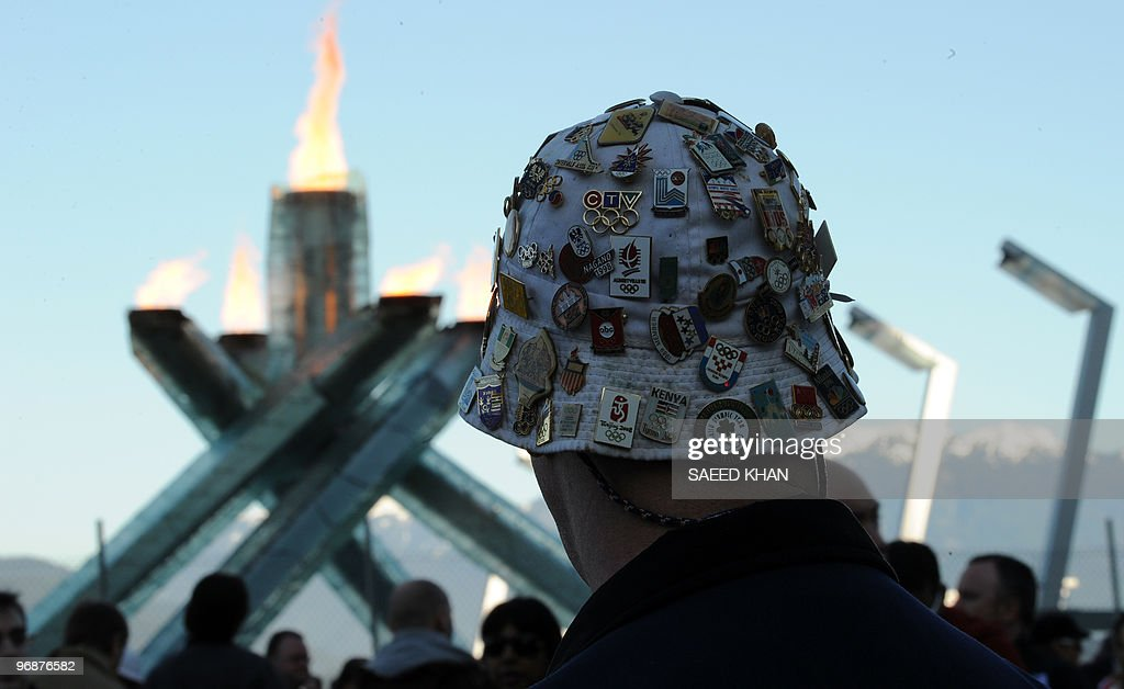 A man wearing a hat with a variety of pins waits for customers outside the Main Press Center on the seventh day of the Winter Olympics in Vancouver...