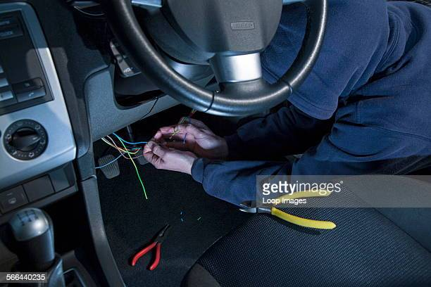 A man wearing a hoody hot wiring a car