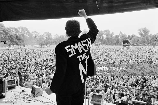 A man wearing a jacket with the slogan 'Smash The NF' gives a clenched fist salute to the crowd from the stage during a concert by English roots...