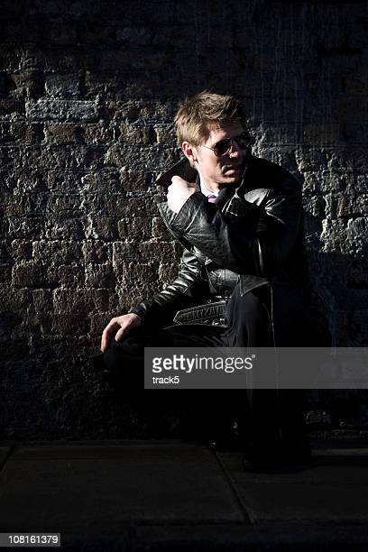 Man wearing a leather jacket sitting in front of brick wall
