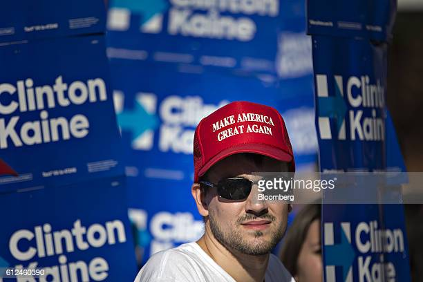 A man wearing a 'Make America Great Again' hat stands amongst campaign signs in support of Hillary Clinton 2016 Democratic presidential candidate...