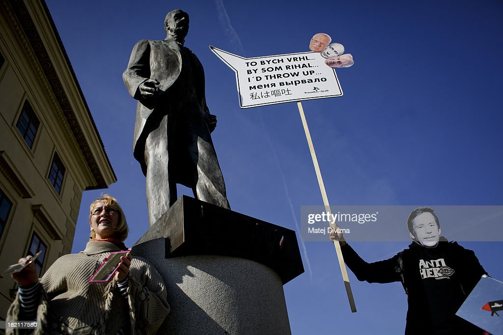 A man wearing a mask, depicting former Czech President Vaclav Havel, holds banner that reads 'I'd throw up' in five languages and shows headshots of former Czech President Vaclav Klaus, Russian President Vladimir Putin and Czech President Milos Zeman as he stands under the statue of the first President of Czechoslovakia T. G. Masaryk during a protest against Czech President Milos Zeman on the Czech Statehood Day, September 28, 2013 in Prague, Czech Republic. Protest was for self-reflection of Milos Zeman and against threat of Russian influence and power.