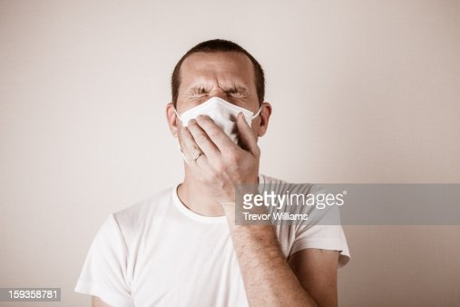 A man wearing a mask holding his nose in pain : Stock Photo