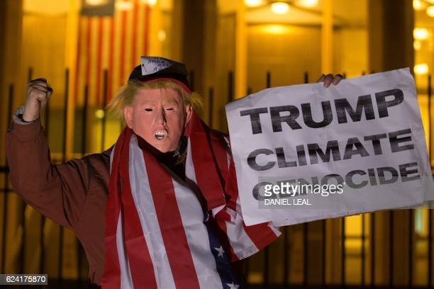 A man wearing a mask portraying newly elected US presidentelect Donald Trump poses with a sign during a demonstration against Trump's vow to withdraw...