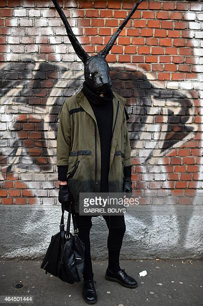 A man wearing a mask poses in the street before the show for fashion house Fendi at the women Fall / Winter 2015/16 Milan's Fashion Week on February...