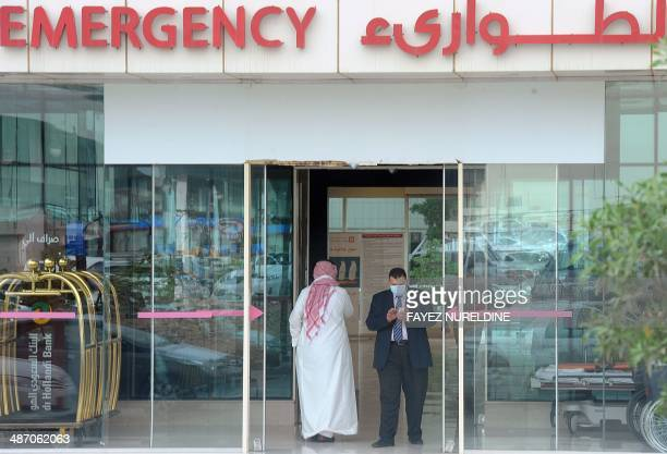 A man wearing a mouth and nose mask checks his phone as he leaves the hospital's emergency department on April 27 2014 in the Saudi capital Riyadh...
