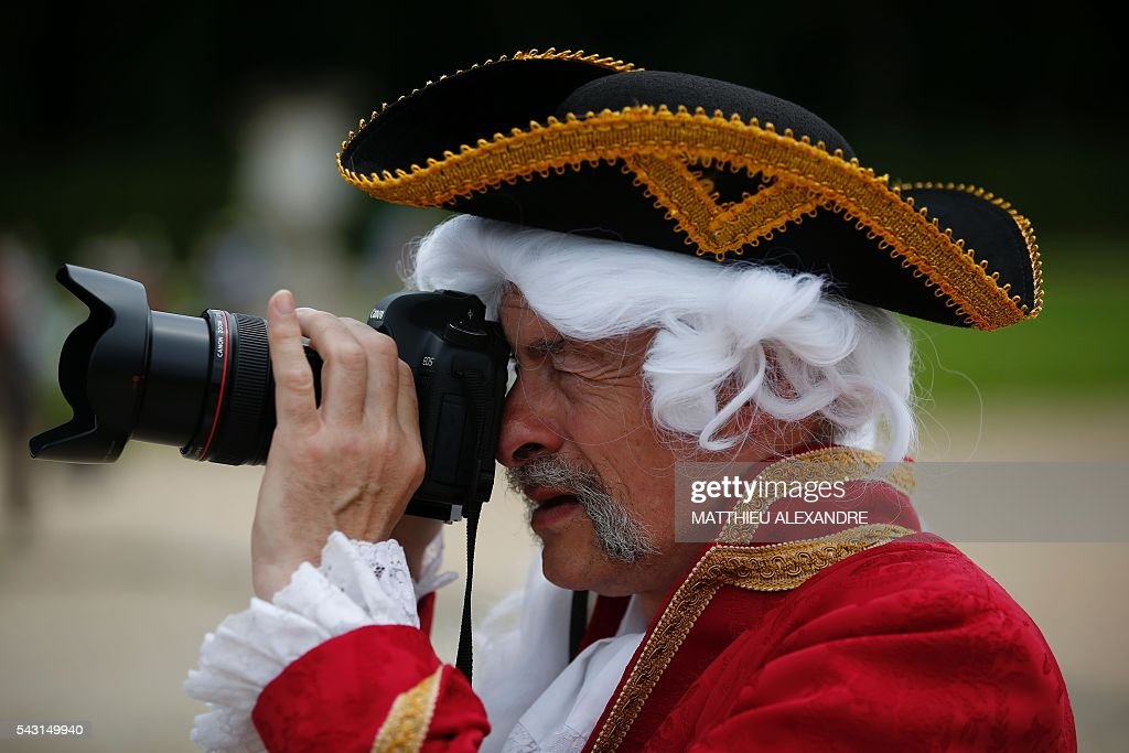 A man wearing a period costume takes a picture during the annual Grand Siecle day event, a rendez-vous for costume passionates, at the Chateau de Vaux-le-Vicomte (Vaux-le-Vicomte castle) in Maincy near Paris on June 26, 2016. / AFP / MATTHIEU