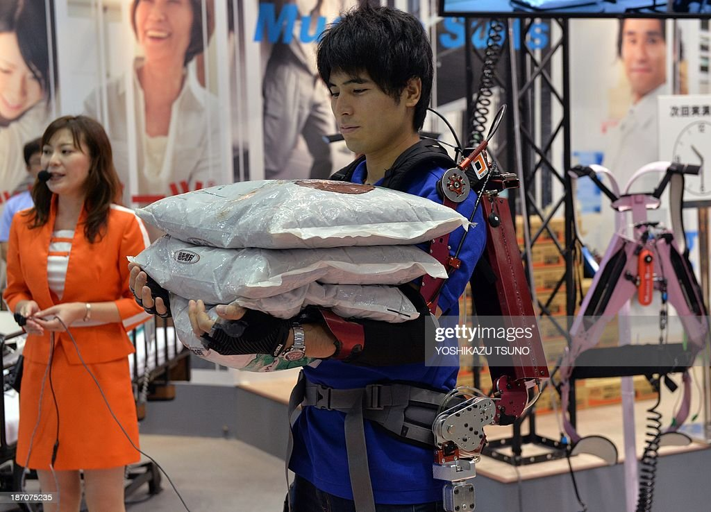A man wearing a power suit called a 'Muscle Suit' with artificial muscles powered by compressed air, holds heavy bags for a demonstration at the annual International Robot Exhibition in Tokyo on November 6, 2013. The Muscle Suit, developed by Hiroshi Kobayashi, professor of the Science University of Tokyo, is used for muscle labor and nursing care. AFP PHOTO / Yoshikazu TSUNO