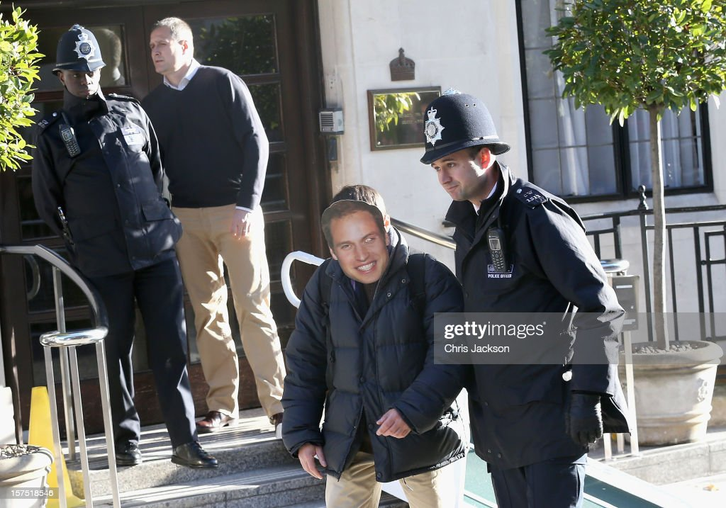 A man wearing a Prince William, Duke of Cambridge mask is escorted away by a police officer from the King Edward VII Private Hospital on December 4, 2012 in London, England. Catherine, Duchess of Cambridge spent her first night in the hospital after yesterday's announement of her pregnancy and the fact she was suffering from hyperemesis gravidarum or acute morning sickness.