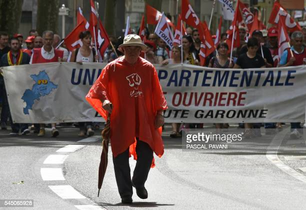 A man wearing a rain coat reading FO walks in front of protesters holding a banner during a demonstration against proposed government labour and...
