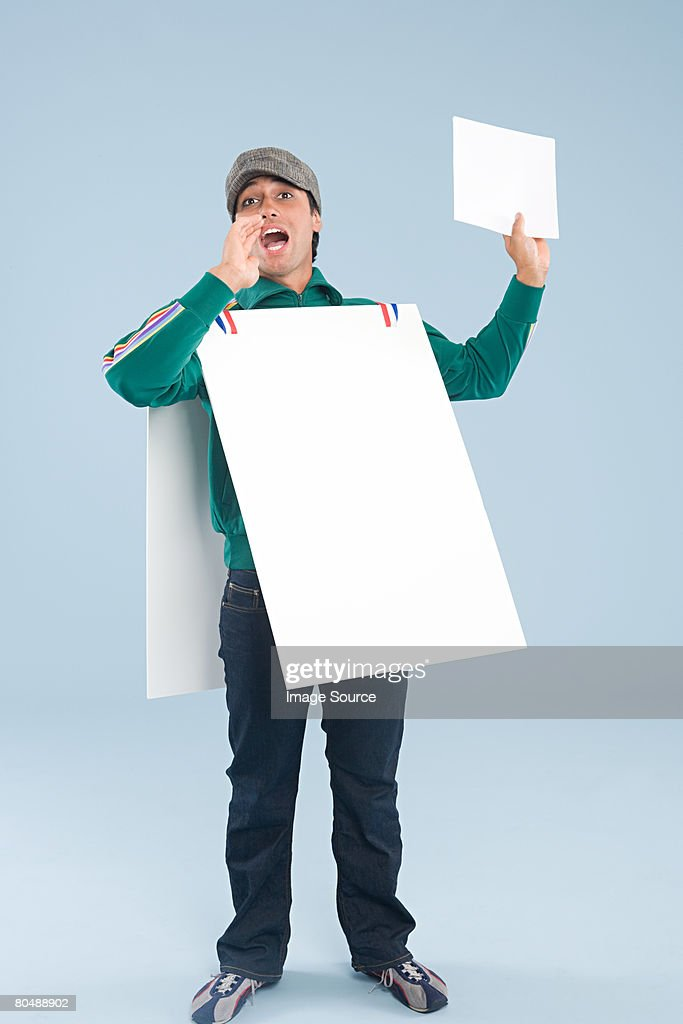 A man wearing a sandwich board : Stock Photo