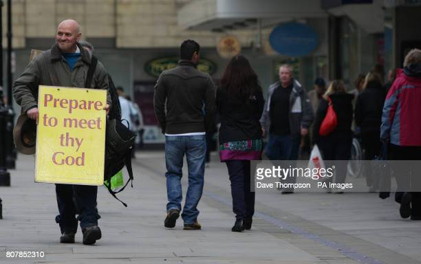 A man wearing a sandwich board walks amongst shoppers in Bolton town centre