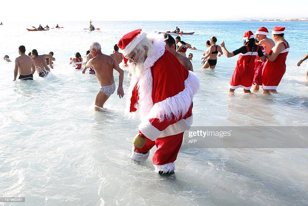 A man wearing a Santa Claus costume stands in the Mediterranean Sea on December 8, 2012 in Nice, southern France. AFP PHOTO / JEAN CHRISTOPHE MAGNENET