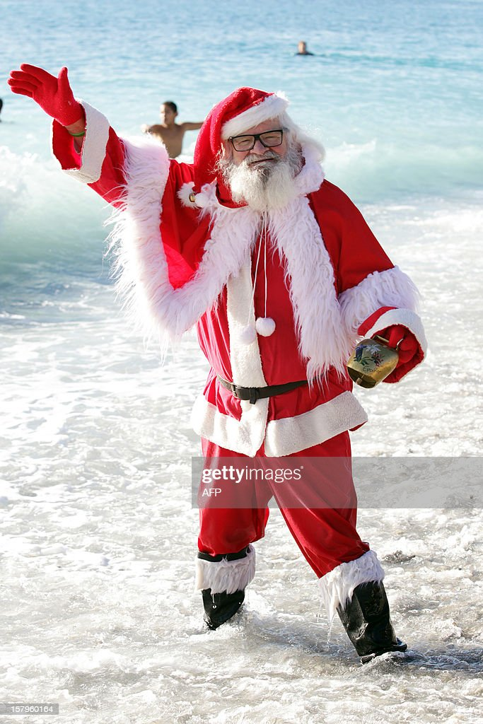 A man wearing a Santa Claus costume waves as he stands in the Mediterranean Sea on December 8, 2012 in Nice, southern France.