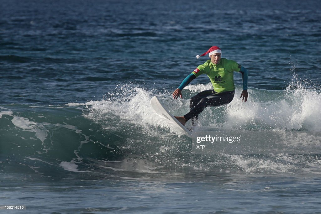 A man wearing a Santa hat practices surf at the beach of Las Americas on the Spanish Canary Island of Tenerife on December 11, 2012. AFP PHOTO / DESIREE MARTIN
