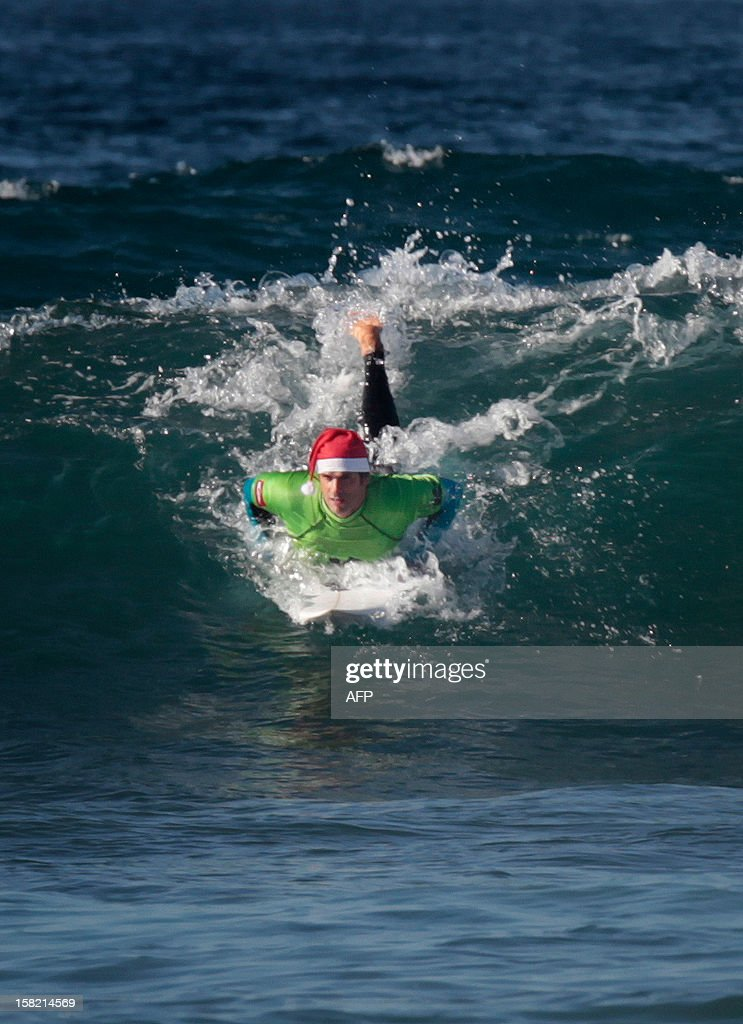 A man wearing a Santa hat practices surf at the beach of Las Americas on the Spanish Canary Island of Tenerife on December 11, 2012.
