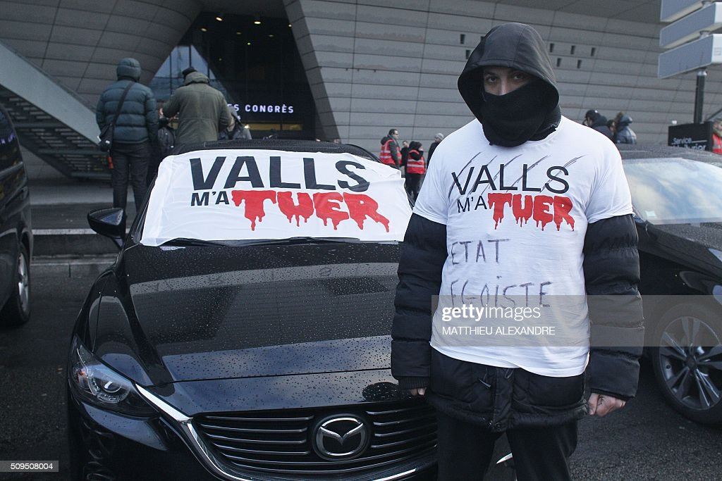 A man wearing a shirt reading 'Valls killed me - Selfish State' stands by his car as drivers of Uber and other ride-hailing companies, known in France as 'voitures de tourisme avec chauffeur' (VTC), a class of companies that allow passengers to book rides with independent professional chauffeurs, gather at Porte Maillot in Paris on February 11, 2016, to defend jobs they believe are threatened by measures the government recently announced in favor of taxis. / AFP / MATTHIEU ALEXANDRE
