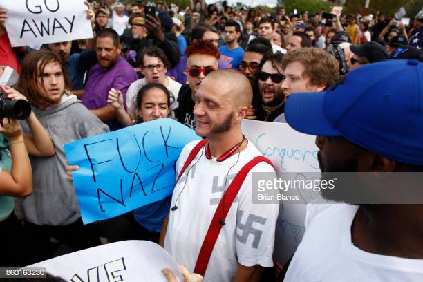 A man wearing a shirt with swastikas is forced away from the scene by the crowd moments before being punched by an unidentified member of the crowd...