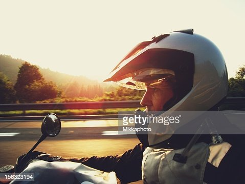 Man wearing a silver helmet riding a motorcycle at sunset