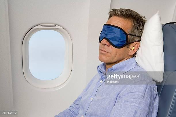 A man wearing a sleep mask sleeping on a plane