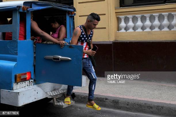 A man wearing a sleeveless sweater with the US flag design gets out of a van in Havana on November 8 2017 Tighter restrictions on US travellers to...