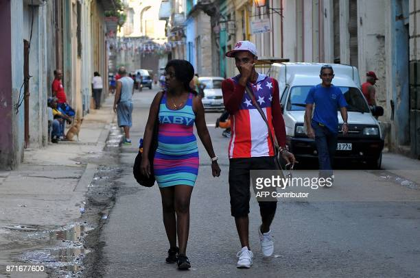 A man wearing a sleeveless sweater with the US flag design walk in Havana on November 8 2017 Tighter restrictions on US travellers to Cuba will go...