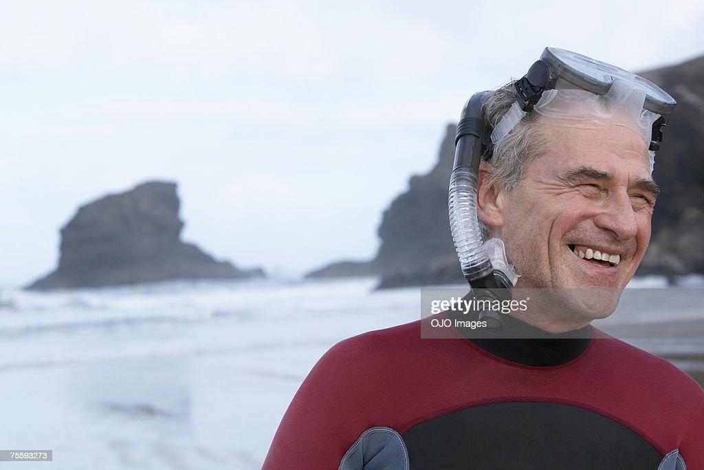 Man wearing a snorkel on a beach : Stock Photo