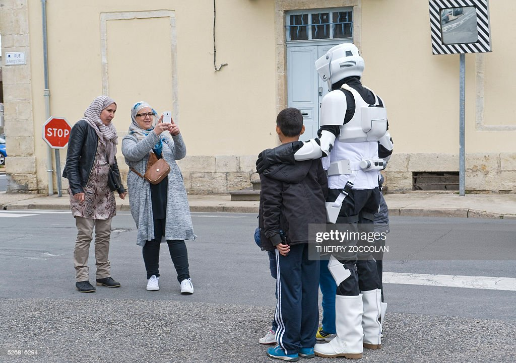 A man wearing a storm trooper costume poses for a picture during a Star Wars convention in Cusset, on May 1, 2016. / AFP / Thierry Zoccolan