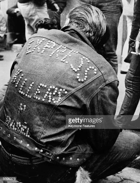 A man wearing a studded denim jacket bearing the words 'Express Killers' attends a Teddy Boy convention in Zurich