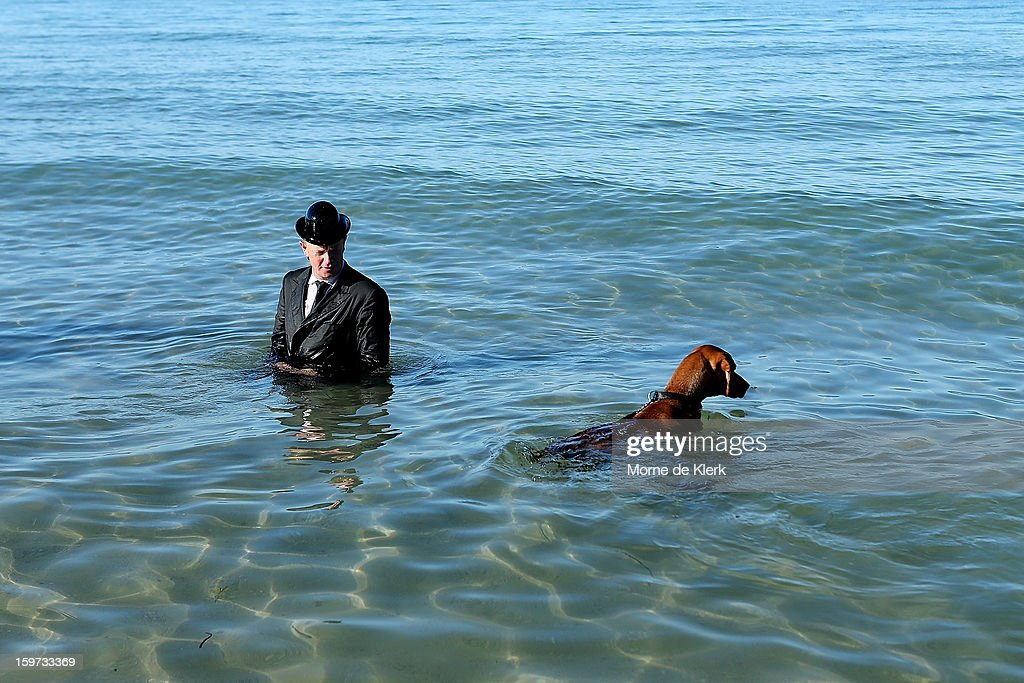 A man wearing a suit and bowler hat stands in the water after taking part in an art installation created by surrealist artist Andrew Baines on January 20, 2013 in Adelaide, Australia.