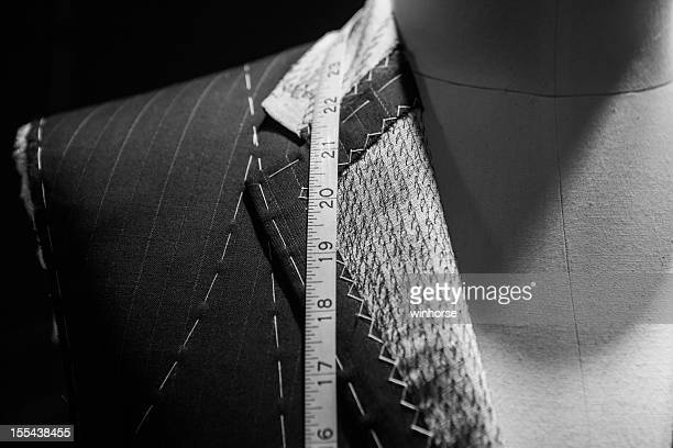 Man wearing a suit close-up with tape measure around neck