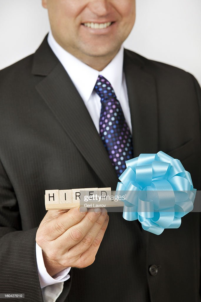 Man wearing a suit holding a sign saying 'hired' : Stock Photo