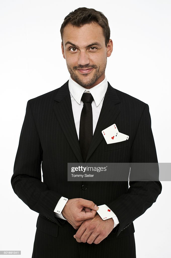 Man wearing a suit pulling an ace of diamonds out of his sleeve with other aces in his pocket