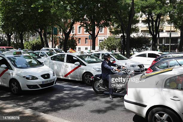 A man wearing a suit rides a motorbike among taxis on the Paseo del Prado on July 3 2012 in Madrid Spain Despite having the fourth largest economy in...