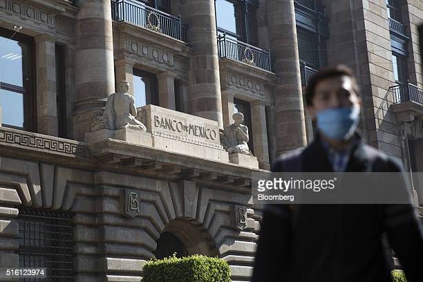 A man wearing a surgical mask walks outside Mexico's central bank headquarters the Banco de Mexico in Mexico City Mexico on Tuesday March 15 2016...