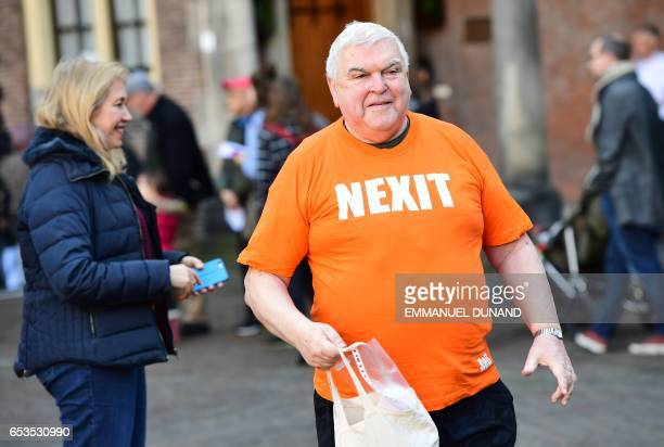 A man wearing a teeshirt reading 'Nexit' walks during the Dutch general elections in The Hague on March 15 2017 Millions of Dutch flocked to the...