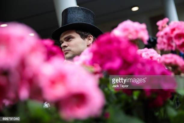 A man wearing a top hat walks past a box of pink flowers at Royal Ascot at Ascot Racecourse on June 22 2017 in Ascot England The fiveday Royal Ascot...