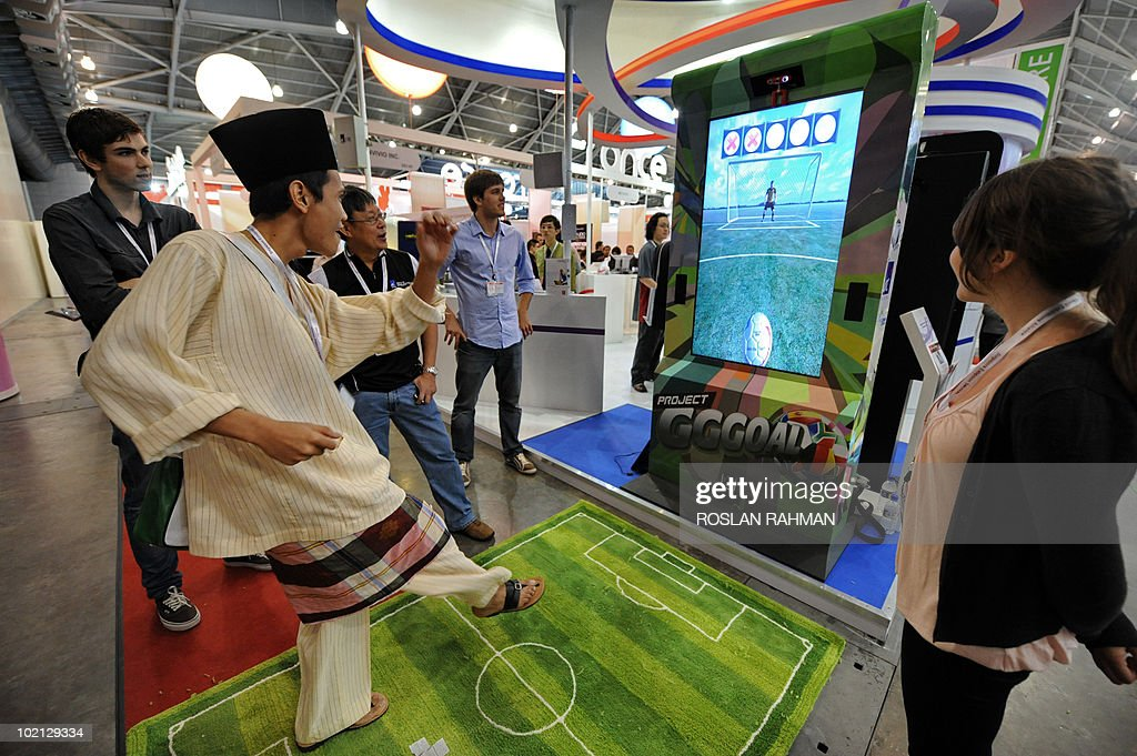 A man wearing a tradition Malay dress plays a virtual soccer game at the CommunicAsia 2010 conference and exhibition show in Singapore on June 16, 2010. The exhibition showcases the newest technologies, products and solutions, featuring almost 2000 exhibiting companies from 57 countries and region.