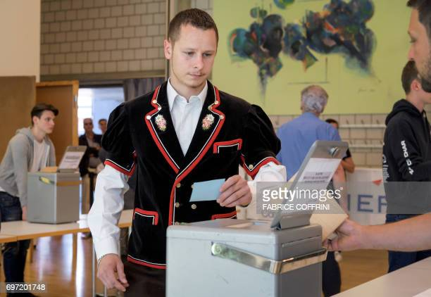 A man wearing a traditional outfit casts a ballot during an historical anticipated vote on June 18 2017 in Moutier northern Switzerland Moutier vote...