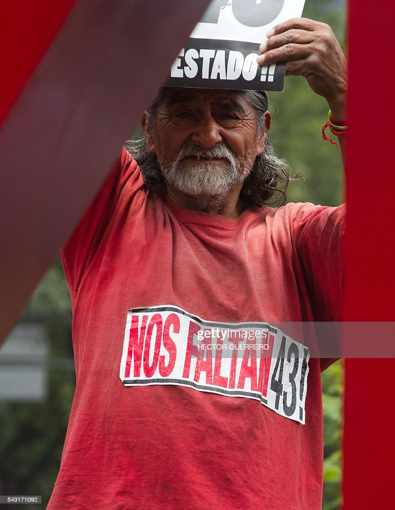 A man wearing a T-shirt reading 'We are missing 43' -referring to the 43 missing students of Ayotzinapa- participates in a demo in support of the National Coordination of Education Workers (CNTE) teachers' union, and against an education reform launched by the government along Reforma Avenue in Mexico City on June 26, 2016. / AFP / Hector GUERRERO