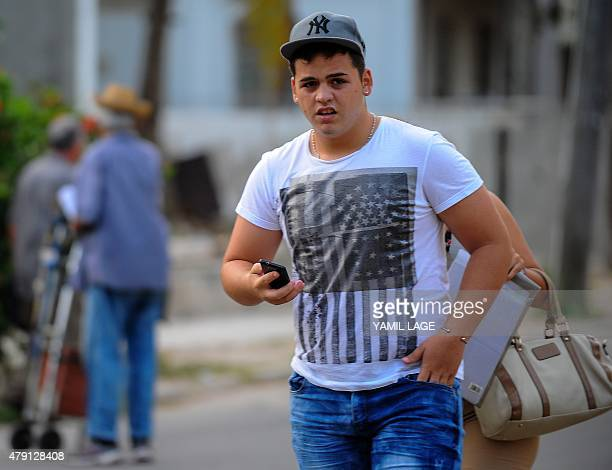A man wearing a tshirt with a US flag design walks along a street of Havana on July 1 2015 President Barack Obama is expected to unveil today a...