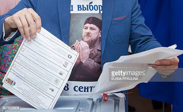 A man wearing a Tshirt with an image of Chechnya's leader Ramzan Kadyrov casts his ballots at a polling station during parliamentary elections in the...