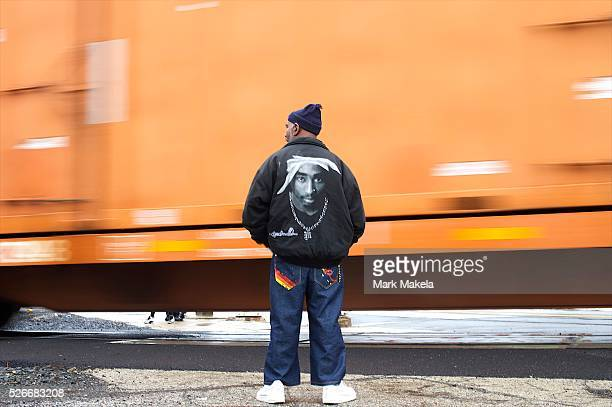 A man wearing a Tupac Shakur jacket watches a freight train pass in Darby PA on April 2 2015