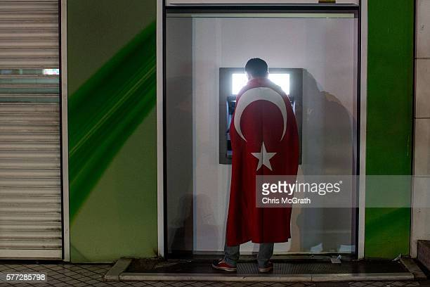 A man wearing a Turkish flag uses an ATM machine while attending rally in Kõzõlay Square on July 18 2016 in Ankara Turkey Clean up operations are...